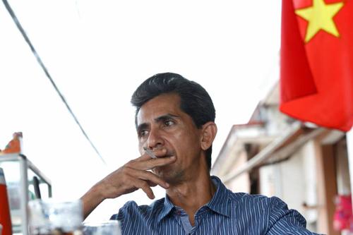Pham Chi Cuong, 47 tuổi, bị trục xuất khỏi Mỹ vào tháng 12/2017, ngồi tại một quán ăn trên hè phố ở TP. HCM vào ngày 20/4. Ảnh: Reuters.